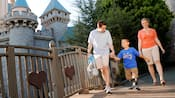 A smiling boy with prosthetic legs walks across a bridge with his mother and father in front of Sleeping Beauty Castle
