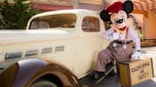 Newsboy Mickey rests his foot on the running board of a classic car on Buena Vista Street