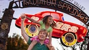 A girl sits on her dad's shoulders near the Radiator Springs Racers sign