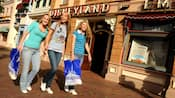 Three women walk down Main Street, U.S.A. with shopping bags.