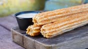 Three carrot cake churros are stacked on a wooden serving board with dipping sauce on the side