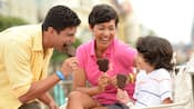 A mother and father enjoy Mickey Ice Cream Bars with their son