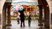 Mickey and boy, both silhouetted, hold hands as they walk through an archway towards Fantasyland