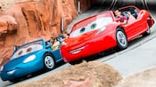 Two vehicles with Guests race around the Radiator Springs track