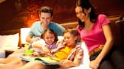 Smiling family reading a book together on a hotel bed with Sleeping Beauty Castle headboard