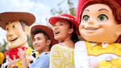 Woody and Jesse from Toy Story pose with a teen girl and boy wearing cowboy hats
