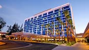 The entrance of Disneyland Hotel is accented by a grove of palm trees at dusk