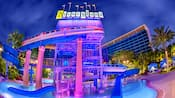 The Monorail waterslide and waterfall glow at night over the pool  area surrounded by hotel towers