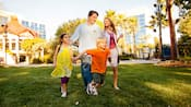 A family of four strolls across a lawn on the grounds of the hotel