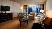 Una cómoda con TV, una mesa de centro ovalada, un sofá, un sillón, una mesa redonda con cuatro sillas y una ventana grande