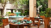 An outdoor dining area with set tables near bushes and a central fountain