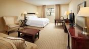 Una cama King Size, sofá cama matrimonial, sillón orejero, mesa de centro, escritorio con silla y cómoda con televisor