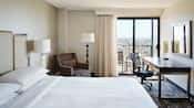 A Marriott hotel guest room includes a queen size bed with leather headboard, comfortable chairs, lamps, a desk and balcony overlooking scenic Anaheim