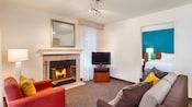 Interior de una habitación tipo departamento, que incluye un área de estar con chimenea, un televisor, un sofá pequeño, una silla tapizada y una conexión mediante una puerta a una habitación independiente