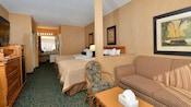 Área de estar con un sofá cama junto a dos camas Queen Size, frente a una cómoda con TV de pantalla plana