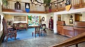 Castle Inns lobby features a check in desk, stained glass window, iron chandelier and medieval decor