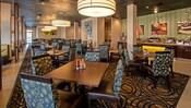Un restaurante en el hotel que cuenta con mesas y sillas situadas sobre una alfombra con diseño, además de una decoración moderna en los alrededores