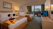 A Mickey plush toy sits on a double bed and, beyond, another queen bed, a round table and balcony