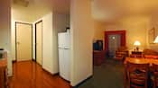 A living room next to a kitchenette with a refrigerator and a door leading to a bedroom