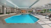 Large indoor swimming pool with patio tables and chairs framed with indoor plants and glassed walls