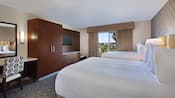 Two queen beds, curtained balcony, built in wooden armoire, desk and chair, wall mounted TV and mirror