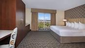 Cama King Size contemporánea con respaldo acolchado y almohadas, armario, escritorio y silla con vista del balcón