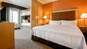 A modern family suite includes bunk beds, a king size bed, side tables, lamps, a TV and dresser