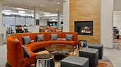 The hotel lobby features a fireplace, circular couch, coffee table, ottomans and a separate dining area