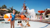 A group of kids and adolescents play in a swimming area with slides, pools and fountains