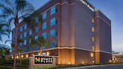 The exterior of Hyatt Place at Anaheim Resort/Convention Center at night surrounded by palm trees