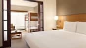 An illuminated family-style suite at Hyatt Place at Anaheim Resort/Convention Center with two sleeping areas featuring a king-sized bed and twin-bunk beds
