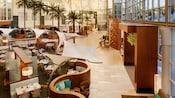 Tall windows line the lobby as sunlight illuminates a dining area at the Hyatt Regency Orange County