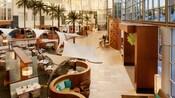Altas ventanas bordean el lobby mientras la luz del sol ilumina un área de comida en Hyatt Regency Orange County