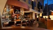 Taburetes bordean un mostrador mientras están dando un partido de básquetbol en una TV en un bar de Hyatt Regency Orange County