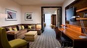 Un salón con un sofá cama, butaca, escritorio, TV de pantalla plana y, más allá, puertas abiertas a una habitación