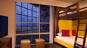 Una litera junto a una pared de ventanas y frente a una TV de pantalla plana sobre una cómoda