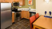 A kitchen with a refrigerator, stove, microwave sink, dishwasher and a table with 2 chairs