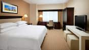 A king sized bed features crisp bedding with an armoire, desk, chairs and modern art decorating the room