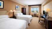 This modern, sophisticated room features 3 chairs, an armoire, desk, side tables and 2 queen size beds