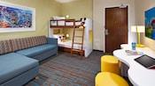 Sala de estar de la suite para niños con sofá, literas Twin Size y un escritorio grande con lámpara y taburetes