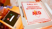 A Cast Member accesses a well-marked automated external defibrillator available in a hotel hallway