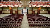 An expansive hotel meeting room with seating set up for several hundred Guests