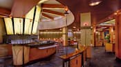 A dramatic, large circular bar with bar chairs surrounded by several more intimate seating areas