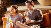 A couple with cocktails sit on an outdoor wicker sofa and enjoy a movie