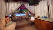 Inside a private poolside cabana featuring a couch, lounge chairs, bar console and a TV