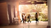 A family of four playfully sneaks down an outdoor corridor at Disney's Grand Californian Hotel & Spa