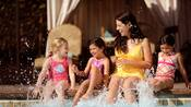 A mom and 3 young girls sit at the edge of the pool and splash their feet