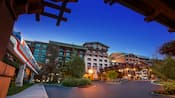 Disney's Grand Californian Hotel & Spa rises above the valet parking area as the monorail goes past