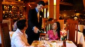A server pours wine for a couple sitting at a dinner table at Napa Rose restaurant