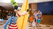 A family of four walks by the surfer Goofy statue in the lobby at Disney's Paradise Pier Hotel